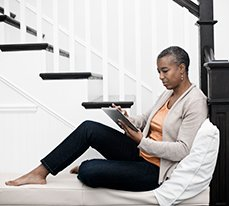 woman sitting on stairs looking at PurePoint on a tablet